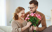 happy loving   couple. husband gives his wife flowers at home