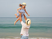 happy family at beach. father and child daughter hug at sea