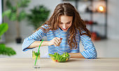 healthy eating. happy young girl eating salad in  morning in kitchen