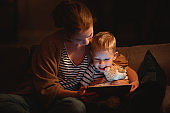 happy family mother and child son with  tablet in evening
