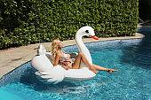beautiful sexy woman with blond hair in elegant bikini relaxing in swimming pool