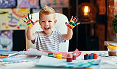 funny child boy draws laughing shows hands dirty with paint
