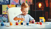 funny child boy draws laughing   with paint