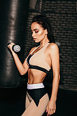 beautiful sexy woman with dark hair in sportive clothes training in gym