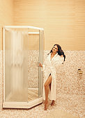 sexy woman with dark hair in white robe relaxing in elegant hotel's bathroom