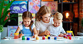 mother and children son  and daughter painting draws in creativity in kindergarten
