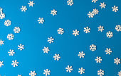 Christmas festive blue background on which are wooden Christmas toys, white snowflakes of different sizes
