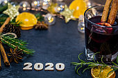 Happy New Year 2020 still life concept on dark slate board with dried oranges, anise stars, cinnamon sticks and evergreen