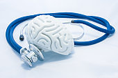Model of human brain with convolutions and blue stethoscope are on white uniform background. Concept photo health or pathological condition of human brain, diagnosing diseases of  nervous system