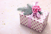 Christmas gift box with spruce branch and pink bunch of berries