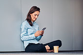 Young business woman uses the phone during a coffee break while sitting on the floor in the office