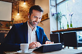 Businessman using tablet in cafe and having phone call on wireless headphones