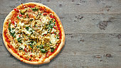 Textured wooden Table with vegetarian pizza