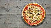 Textured wooden Table with four seasons pizza.