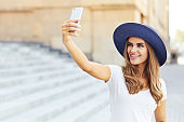 Portrait of young woman taking selfie outdoors