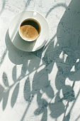 cup of coffee in the morning light, sunlight shadow, morning breakfast minimal concept, top view, copy space