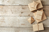 Wrapped christmas presents in paper craft package on vintage wooden background, copy space. stylish gifts, seasonal greetings, concept of holiday preparation