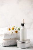 Spa and wellness setting. Composition with chamomile flowers and cosmetic bottle of essential oil serum and cream in zero waste pacage on white background