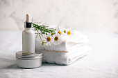 Chamomile flowers and cosmetic bottles of cream and serum essential on white background. Space for text. Zero waste cosmetic package concept