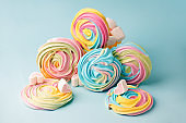 Colorful unicorn rainbow color meringue lollipops candy on blue background. Flat lay. Summer sweet abstract Minimal concept. Sweetness abstraction sur