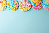 meringues in unicorn rainbow pastel colors, frame and copy space on blue backgound, simple minimal