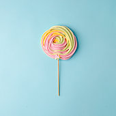 Colorful unicorn rainbow color meringue lollipop candy on pale on blue background. Flat lay. Summer sweet Minimal concept.