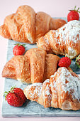 Delicious breakfast with fresh croissants and ripe berries on marble plate, selective focus