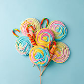 Crispy unicorn rainbow twisted meringue and lolly pops candies on blue background. Concept love of sweet, birthday party, sugar sweets
