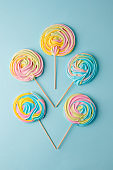 Colorful unicorn rainbow color meringue lollipops candy on pale on blue background. Flat lay. Summer sweet abstract Minimal concept.