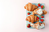 freshly baked croissants on marble cutting board, top view, copy space, breakfast background