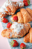 Fresh homemade croissants with strawberry and various toppings. Top view. French bakery concept.