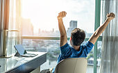 Business achievement concept with happy businessman relaxing in office or hotel room, resting and raising fists with ambition looking forward to city building urban scene through glass window