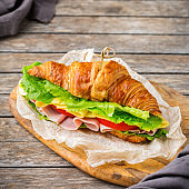 Fresh croissant sandwich with ham, cheese, lettuce and tomato