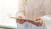 Medical doctor or physician with tablet for patient's health record in hospital or clinic