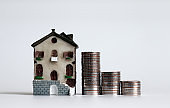 Miniature house and three pile of stepped coins.