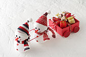 Christmas gift in a small box surrounded by Santa Claus, reindeer and snowman on the snow