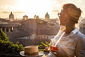 Young woman tourist fashion white dress with spritz cocktail in front of panoramic view of Rome cityscape from campidoglio terrace at sunset. Landmarks, domes of Rome, Italy.