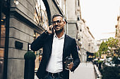 City walk. Technology. Coffee break. Business. Handsome man in suit is talking on the mobile phone, holding a cup of coffee and smiling while walking outdoors