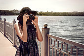 happy stylish woman hipster holding photo camera and smiling at sunny shore near water, summer travel concept, space for text