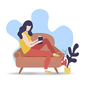 Woman reading book on relaxing sofa at home