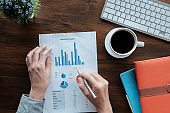 Business accounting concept, Business man using pen pointing  with stock marketing data financial chart,  paper in office.