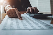Business accounting , Business man using calculator with calculate stock market data chart, tax and budget paper in office.  accounting auditor concepts.