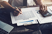 Stock marketing analysis concept, Male using calculator and computer laptop  to analyze stock market chart data application in office.