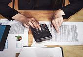Business accounting concept, Business woman using calculator with stock marketing data chart, budget and loan paper in office.