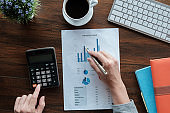 Business accounting concept, Business man using pen pointing  with stock market data financial chart and calculator for calculate finance plan  paper in office.