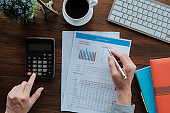 Business accounting concept, Business man using pen pointing  with stock maket data financial chart and calculator for calculate budget planner  paper in office.