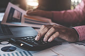 Bookkeeper accounting Concepts, Male  using calculator to calculate with pen and computer laptop to working financial and budget, inspector accountant concept.