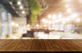 Wood table in blurry background of modern restaurant room or coffee shop with empty copy space on the table for product display mockup.