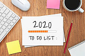 New Year Resolution Goal List 2020 - Business office desk with notebook written in handwriting about plan listing of new year goals and resolutions setting.