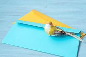 Yellow toy bird and colored envelopes for letters on blue background. Easy abstraction for background.